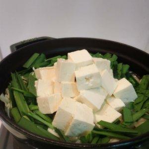 調理中のもつ鍋に野菜を入れた写真